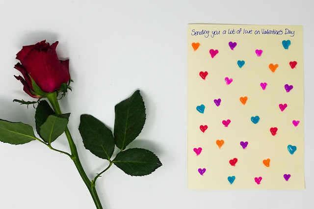 A red rose and a cream card with lots of colourful hearts
