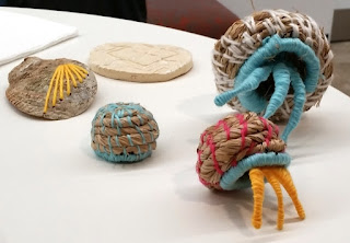Basket weaving techniques created three rounded bowl shapes which, when upturned, become the homes for hermit crabs, the woven legs of which are sticking out of two of the baskets. An abalone shell is embroidered with yellow yarn. Behind them is a flattened piece of ceramic work which has a design carved into it.