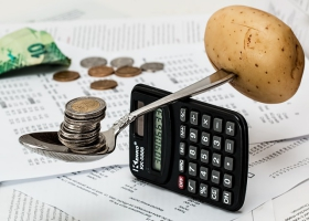 A funny picture of balancing money and a potato with a spoon on a calculator.