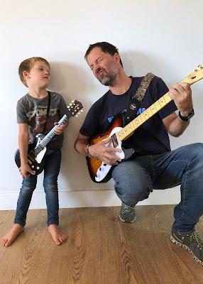 Padre e hijo tocando la guitarra eléctrica