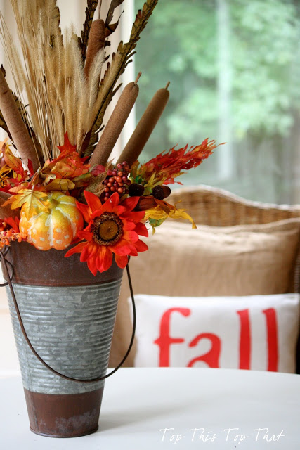 This fall throw pillow pairs well with the vintage bucket flower arrangement.