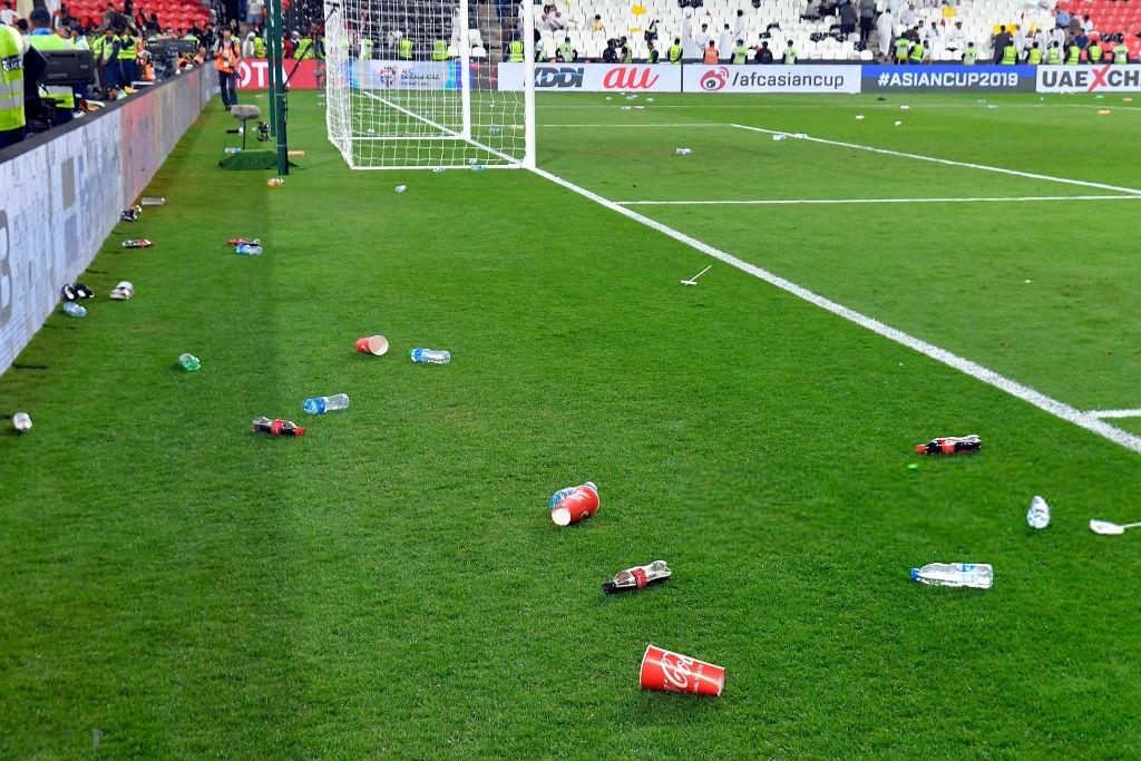 Các lon nước và chai nước trên sân
