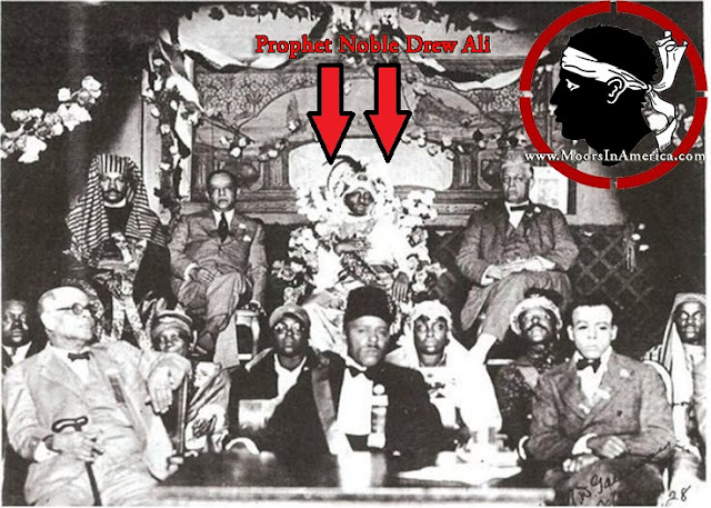Prophet Noble Drew Ali seated surrounded by well-known high powered politicians and movers and shakers in Chicago