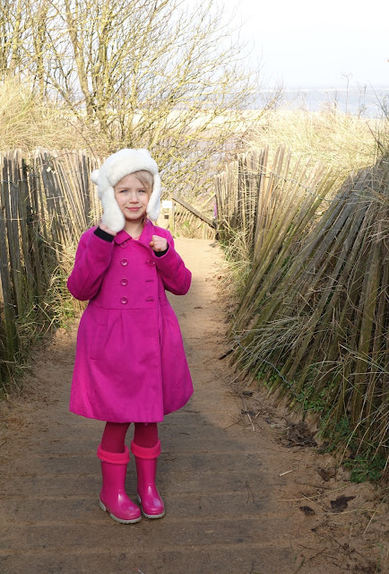 A girl in a fluffy white bear hat, pink coat, pink tights and pink wellies on the path leading to the beach at Wells-Next-The-Sea