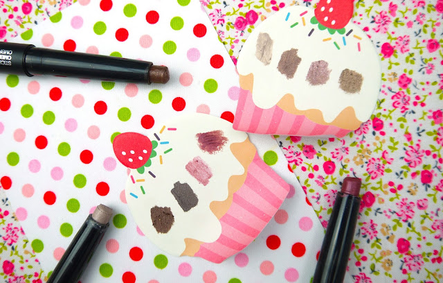 swatches of brown, bronze, and purple kiko cream eyeshadow sticks on a cupcake print paper