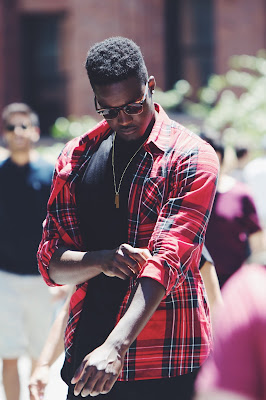 young black man in sunglasses rolls up sleeves of his red flannel