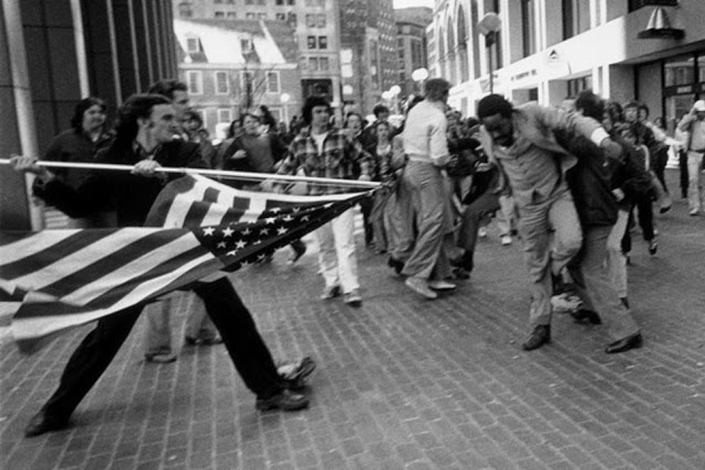 Photo of an angry Joseph Rakes holding the US flag on a pole, charging Ted Landsmark who is being restrained by another man from behind. The Soiling of Old Glory, a Pulitzer Prize–winning photograph taken by Stanley Forman in 1976
