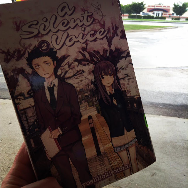 A pale hand holds a paperback copy of A Silent Voice Volume 2 against a rainy backdrop. The book's cover features two Japanese students standing slightly apart on a narrow street lined with cherry blossoms. The boy holds a notebook and looks miserable. The girl seems friendly.