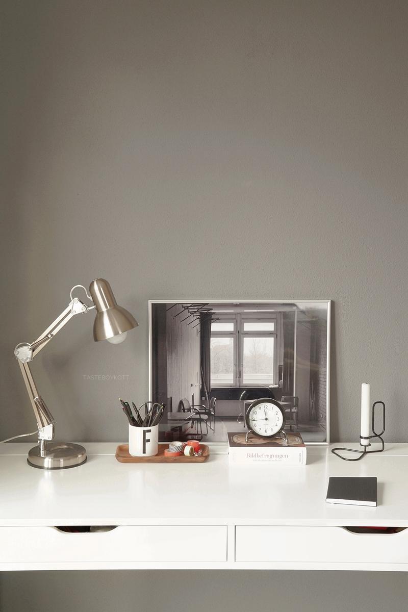 Weißer Schreibtisch vor grauer Wand, moderner reduzierter Arbeitsplatz. Dekoriert mit Tischleuchte, Kunst, Tischuhr in monochromen Farben.