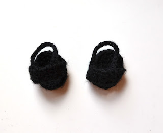 A pair of black crocheted sandals. The sole is oval shaped to match the bottom of the foot. The foot slips into a strap over the instep and another strap secures the sandal around the ankle.