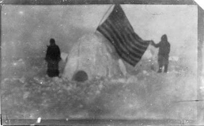 Grainy black and white photo of two men next to an igloo with an American Flag
