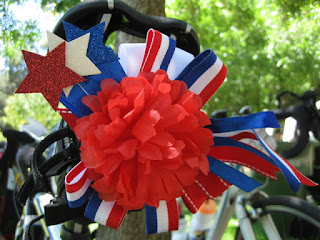 Red flower with red, white, and blue stars and ribbons on my bicycle saddle.