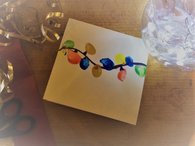 A finger painted christmas card among ribbon, christmas lights etc