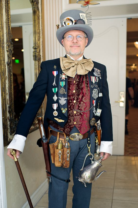 Man cosplaying as steampunk military vet. He wears a top hat, goggles, waistcoat (vet), coat, trousers, gun, cane and military medals, awards and ribbons