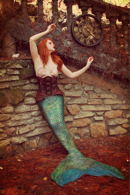 Woman wearing a steampunk mermaid costume, leaning against a stone wall with a clock