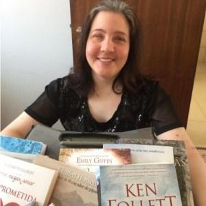 imagem da Lucia com blusa preta segurando uma caixa com varios livros