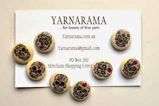 Wooden buttons with decorated skulls painted on them, packaged with Yarnarama's business card.