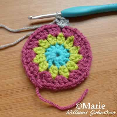Bright color yarn circle with crochet hook adding double crochet stitches