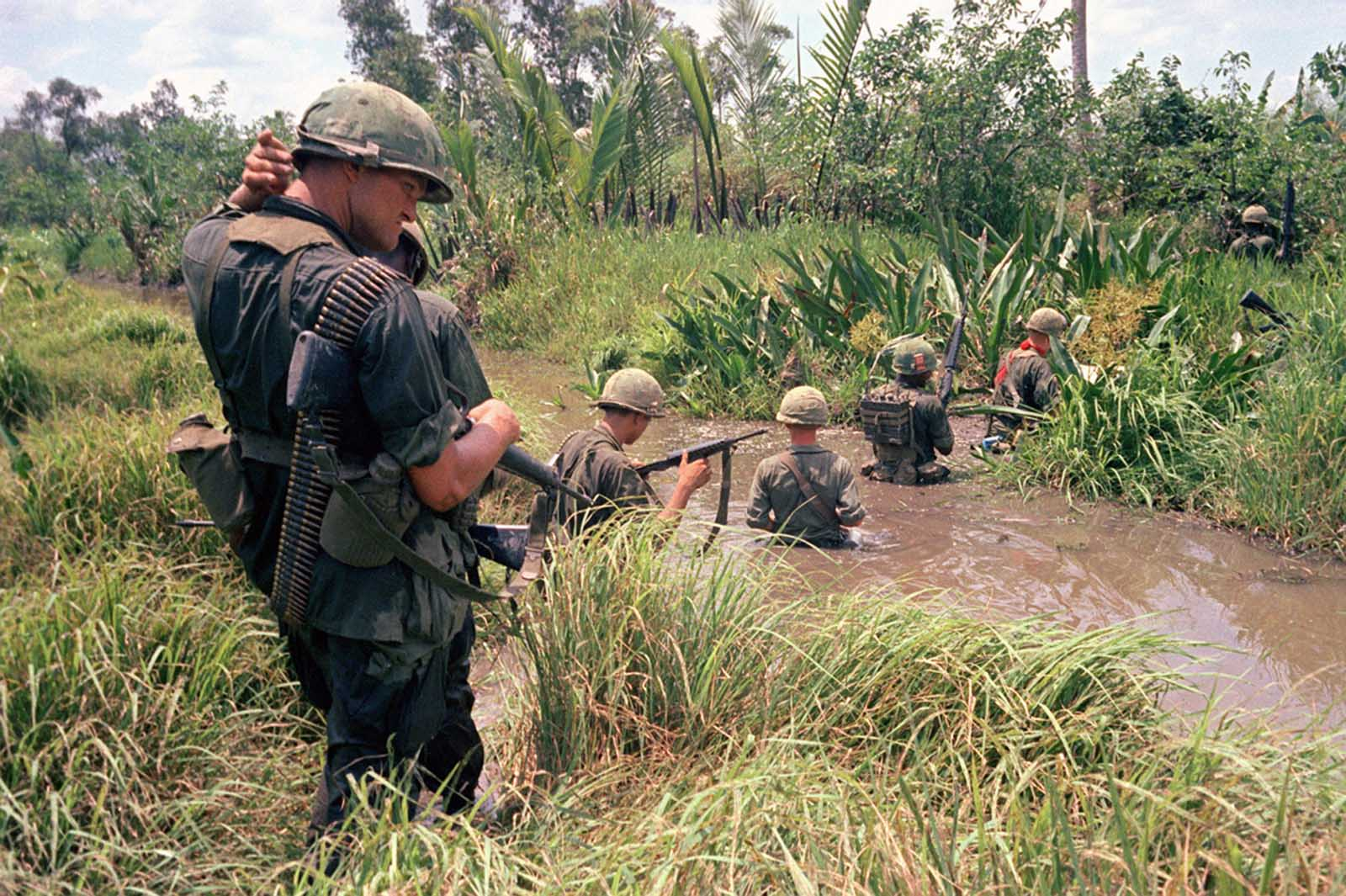 U.S. troops of the 7th and 9th divisions wade through marshland during a joint operation on South Vietnam\u0027s Mekong Delta, in April of 1967.
