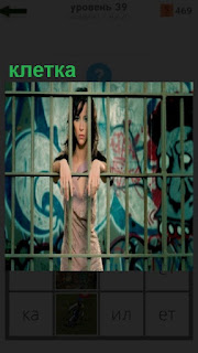 за решеткой в клетке стоит девушка и руки положила на прутья