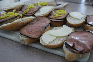 Sliced hoagies topped with sliced cheese, and beef, along with spicy mustard on a cutting board.
