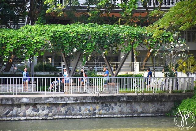 adults walking, pond, plants, trees, residential building