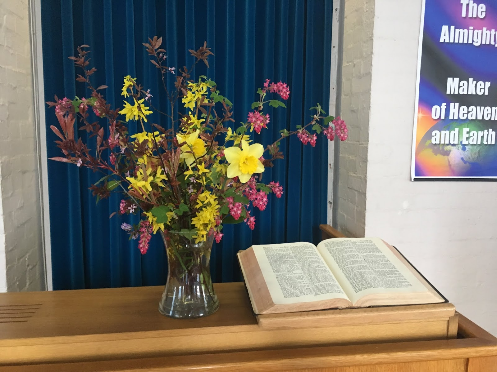 Flowers in a vase on a table with an open Bible next to them