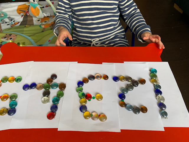 A toddler next to numbers 1 to 5 with glass nuggets tracing the numbers