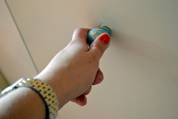 Hand pulling knob on closet