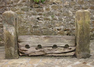 Medieval wooden stocks outside St. Helen's Church, Waddington, Lancashire, England