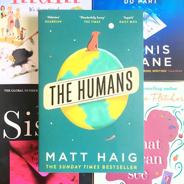 The Humans by Matt Haig book in the centre, laid on top of four other books