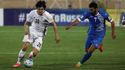 Sardar Azmoun, autor de uno de los goles con los que Irán ganó la clasificación a Rusia 2018, pelea el balón con Azizkeb Khaydarov de Uzbekistán