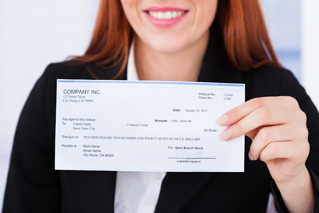 Business woman holding check from company