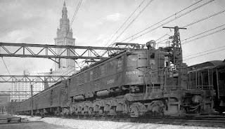From about 1950, a diesel locomotive railroad train with Terminal Tower in far background