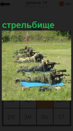 На поляне в ряд на стрельбище лежат военные с оружием и стреляют по мишени