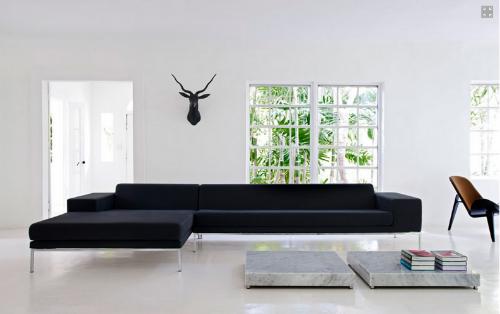 Weiße Wände und ein weißer Boden in einem Wohnzimmer, minimalistisch mit  schwarzen Sofa und Marmortischen eingerichtet