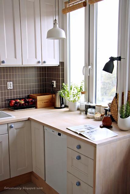 białe szafki, drewniany blat, okno w kuchni