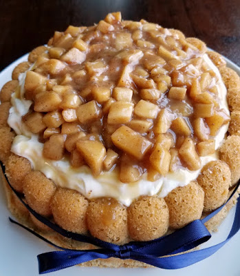 close up of cinnamon sponge filled with cream cheese filling and topped with caramel apples