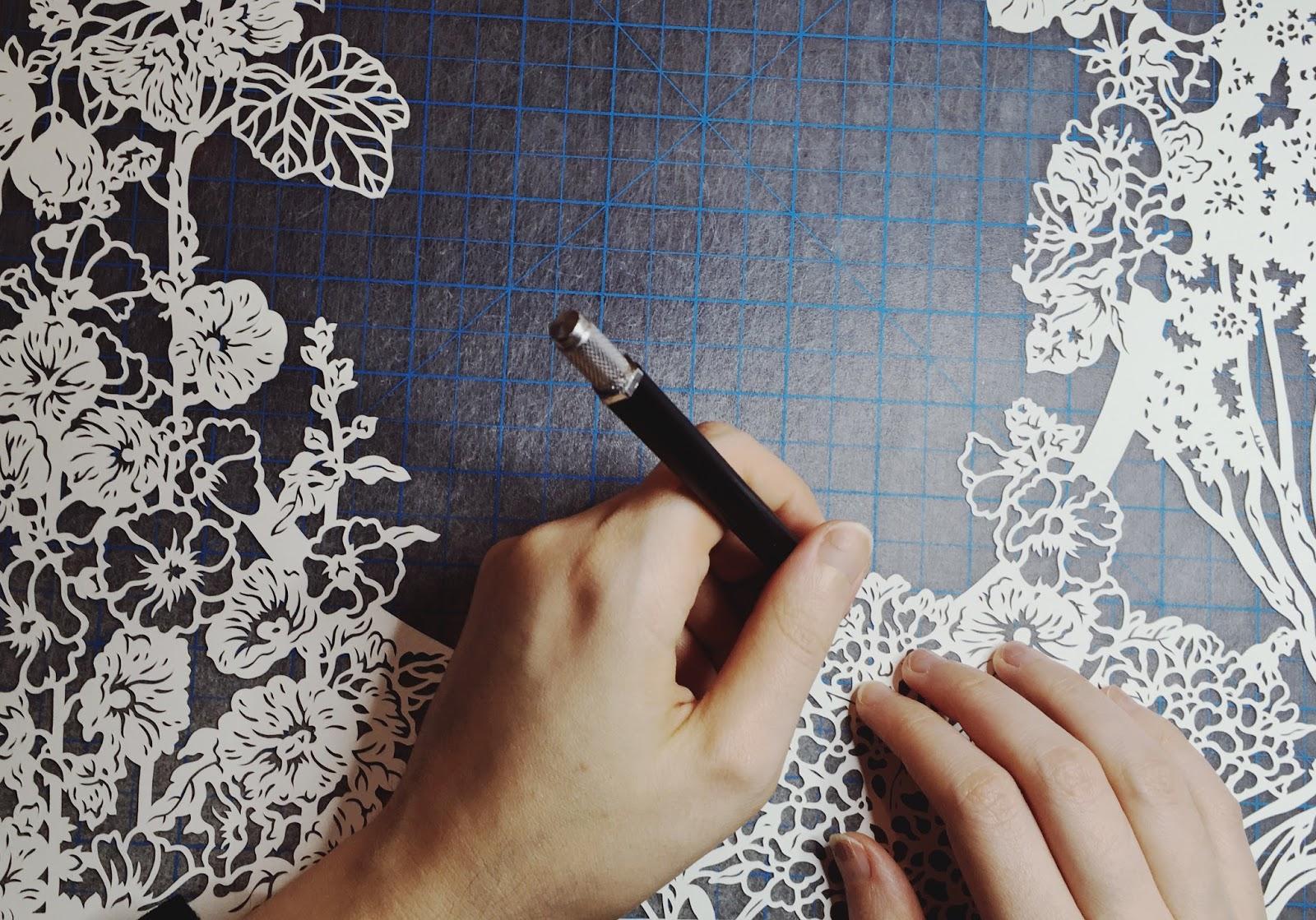 papercut artist Naomi Shiek papercutting a custom design quaker ketubah in her studio