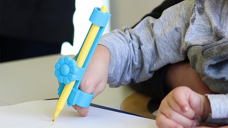 Equipo colabora para ayudar a los niños discapacitados con adaptables y adorables utensilios de escritura