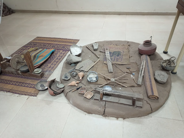 Model of bead making workshop with rug, baked clay work surface, pots, wooden and stone tools and pieces of pottery in Indus Valley civilisation archaeological museum gallery at MS University Baroda