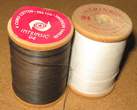 wo old wooden spools of Intrinsic thread size 24 by The American Thread Co.