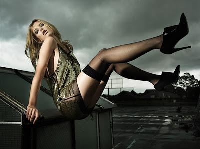 Rubia usando un vestido a  la moda con piernas largas y medias negras