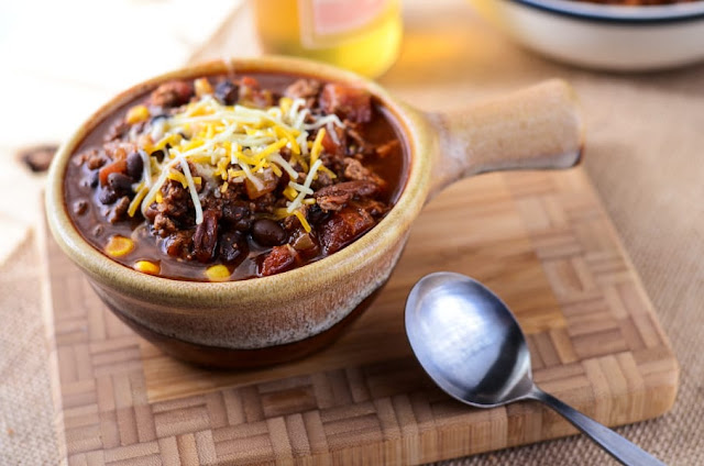Crockpot Mexican Beer Chili in a brown bowl on a wooden cutting board
