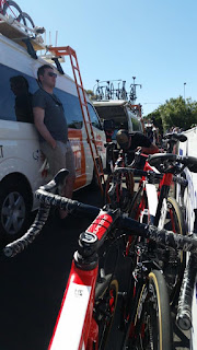 On the left is a row of team buses. A portable ladder is hooked to the side of the bus to enable staff to get onto the roof where the bikes are carried.. A team technician is leaning against the bus. On the right hand side are red bikes lined up against the track barrier. In the background  another team bus still has bikes on its roof and its tailgate is open.