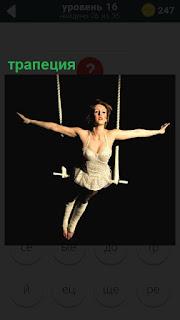 Под куполом цирка женщина на трапеции и раскинула руки в стороны