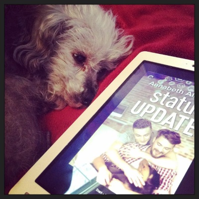 Murchie lays on his side with a white Kobo next to him. The Kobo's screen shows the cover of Status Update, which features two white men on a couch. One hugs the other while simultaneously patting a black and tan dog sprawled in his partner's lap.