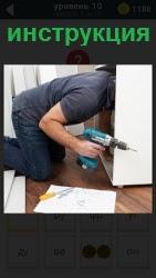 Мужчина с шуруповертом и инструкцией собирает шкафчик