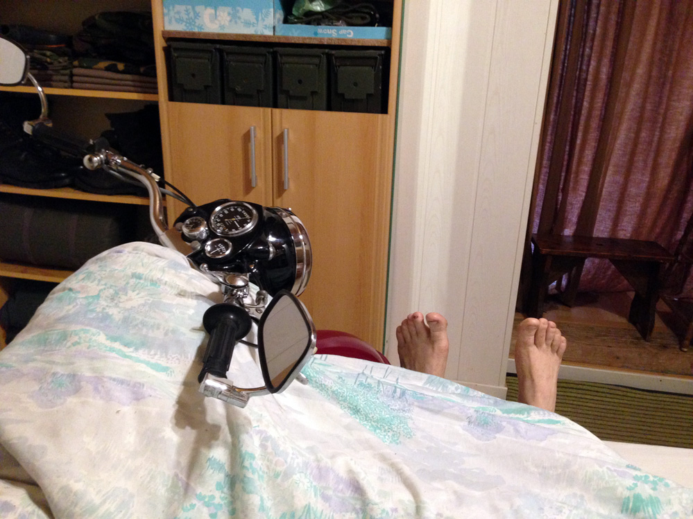 Man and motorcycle in bed.