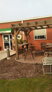 brick patio with wooden pergola and quirky patio chairs and tables outside of Jitters donuts in Sioux City, Iowa